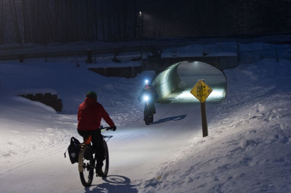 Bicyclists pass on the Chester Creek Trail near its tunnel under Arctic Boulevard on January 18, 2019. (Marc Lester / ADN)