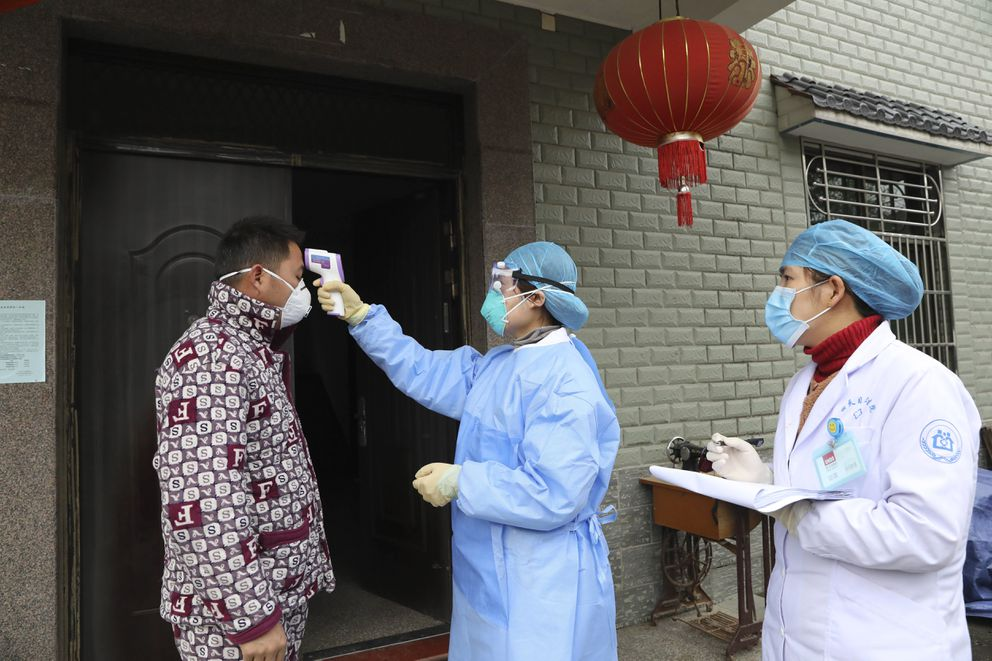 In this Jan. 27, 2020 photo, community health workers check the temperature of a person who recently returned from Hubei Province, center of a virus outbreak, in Hangzhou in eastern China's Zhejiang Province. (Chinatopix via AP)