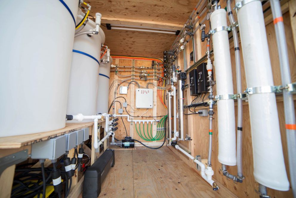The conex that holds the water-treatment equipment sits next to the model home Aaron Dotson, a UAA civil engineering associate professor, and his team of students, including Greg Michaelson and Cara Lucas, have developed an in-home system to treat and reuse water as part of the Alaska Department of Environmental Conservation's Water and Sewer Challenge, an initiative to bring running water and sewage disposal systems to rural villages. (Jonathan Hartford / UAA)