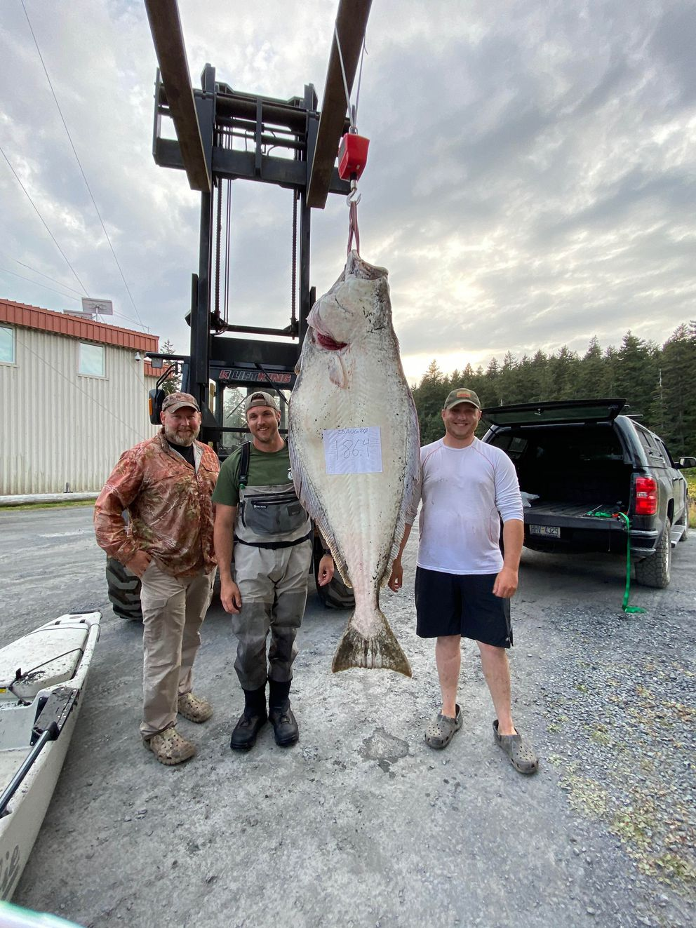 From left, Jeremiah Ericson, Jay Hicks and Jeff Woods stand with the 186.4-pound halibut Hicks landed while fishing from a kayak in Kodiak. (Photo by Sabrina Hicks)