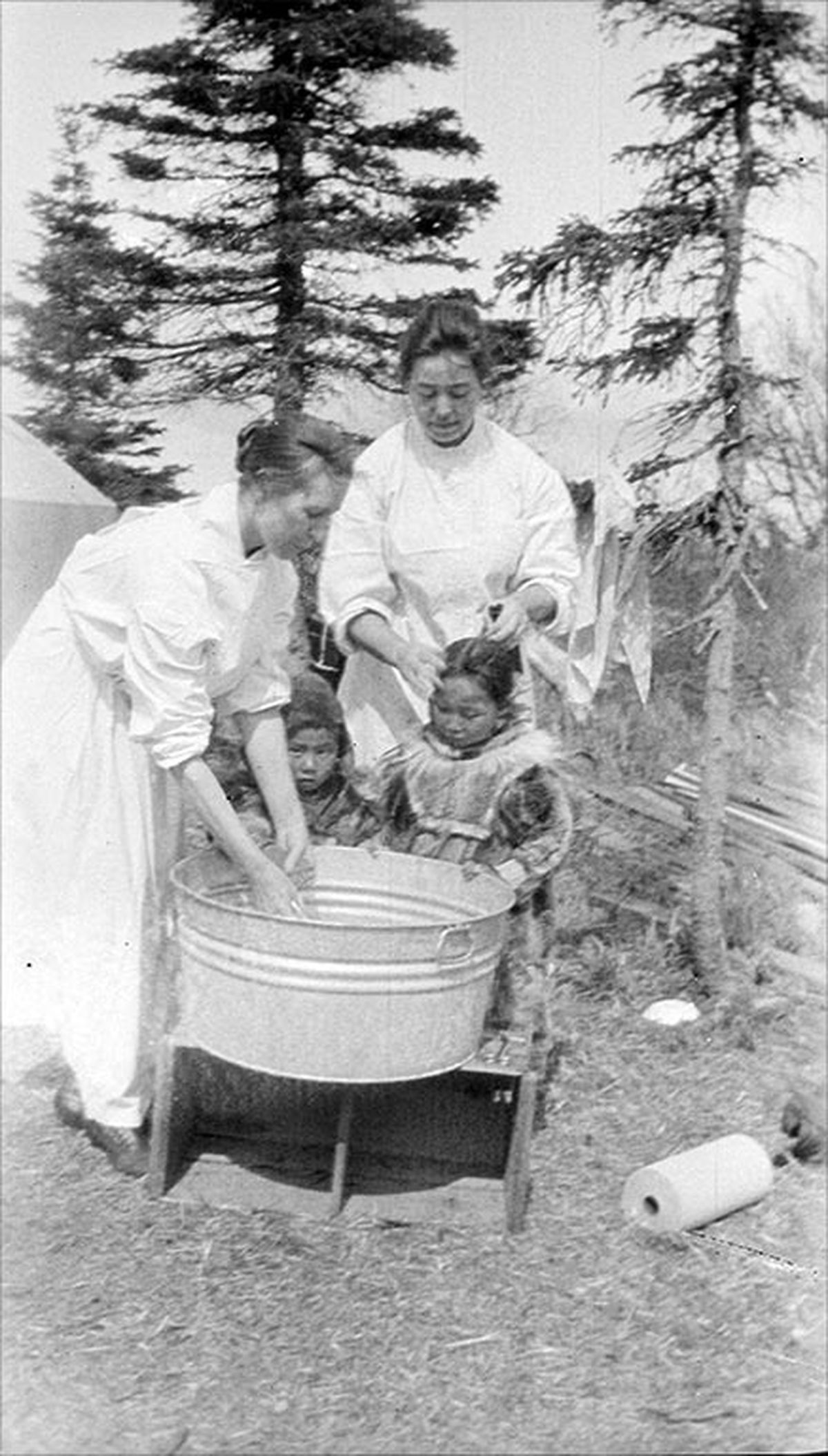 Nurses Mayme Conley and Rhoda Ray help children clean up during the 1919 Spanish Flu pandemic in Bristol Bay. (Dr. Linus H. French photo courtesy Bristol Bay Heritage Land Trust)