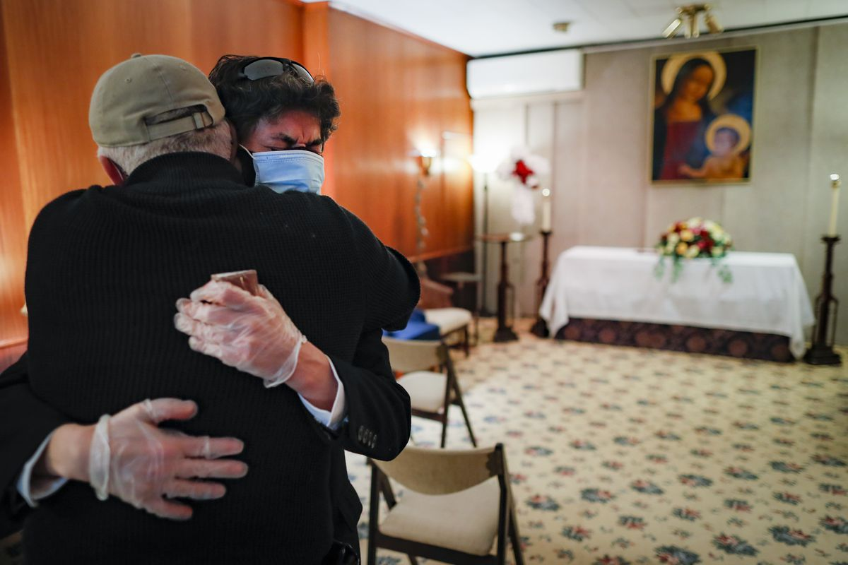 In this Monday, May 11, 2020 photo, Leonardo Cabaña cries in the arms of his friend, Raphael Benevides, beside the casket of his father, Héctor Miguel Cabaña, who died of COVID-19. (AP Photo/John Minchillo)