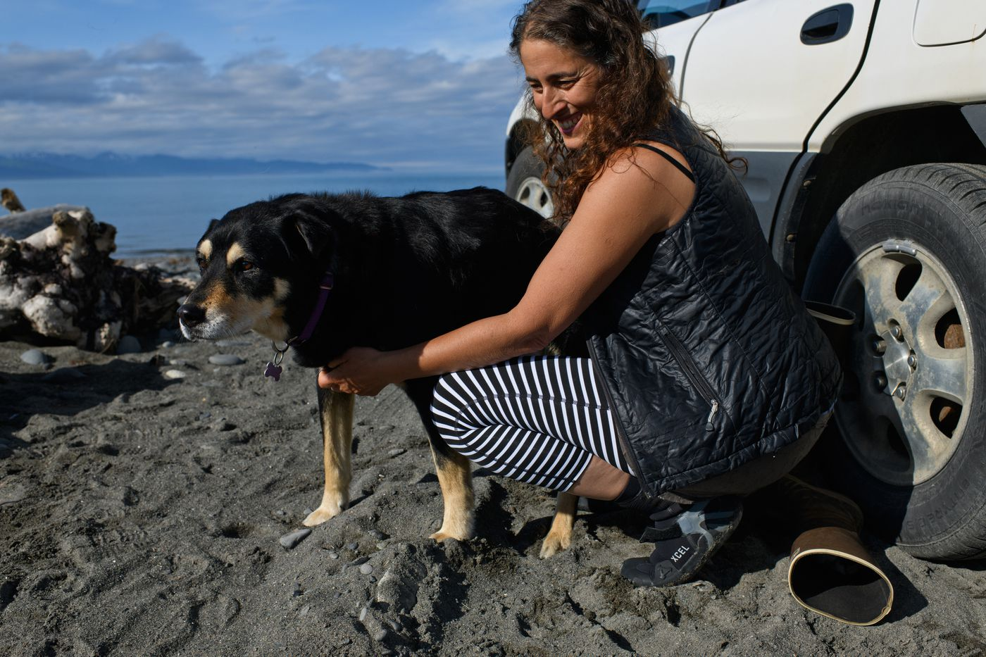 Stephanie Zuniga prepares to paddleboard along Bishop's Beach in Homer as her 14-year-old dog, Moleh, walks along the shore on June 20, 2018. (Marc Lester / ADN)