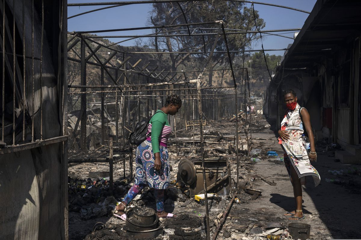 Two migrant women stand at the burned Moria refugee camp on the northeastern Aegean island of Lesbos, Greece, on Wednesday, Sept. 9, 2020. A major overnight fire swept through Greece's largest refugee camp, that had been placed under COVID-19 lockdown, leaving more than 12,000 migrants in emergency need of shelter on the island of Lesbos. (AP Photo/Petros Giannakouris)