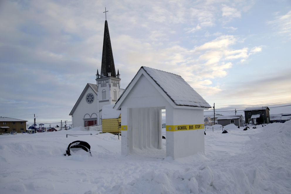 In this Feb. 14, 2019, photo, a school bus stop stands in front of Old St. Joe's Hall, built in 1901 by a Jesuit priest in Nome, Alaska. (AP Photo/Wong Maye-E)