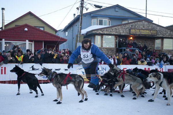 John Baker walks his team across the finish line in Nome.