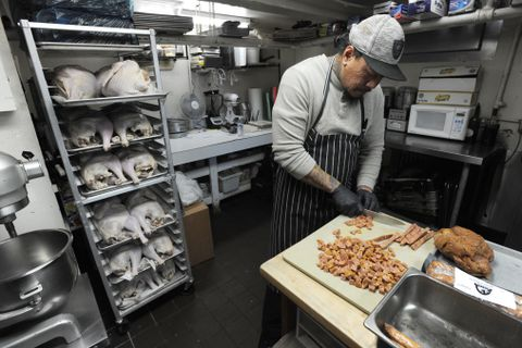 Jack Amon, partner and chef at The Marx Bros Cafe, trusses a sage-brined ready-to-roast turkey on Wednesday, Nov. 15, 2017, for their takeout Thanksgiving dinners, which can be ordered online. (Bill Roth / Alaska Dispatch News)
