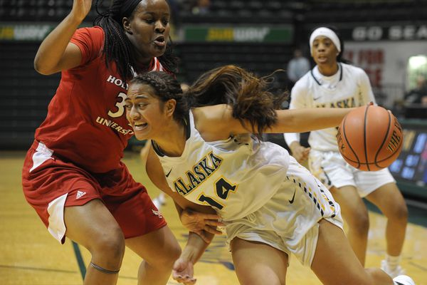 Onjalise Carley-Hilliard, Holy Names, defends as Sala Langi, of UAA, drives the baseline during the Seawolf Hoops Classic at the Alaska Airlines Center in Anchorage, Alaska on Friday, Nov. 17, 2017. (Bob Hallinen / ADN)