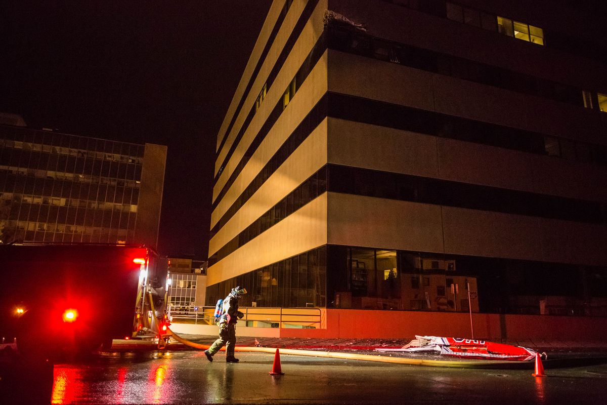 Anchorage Fire Department personnel secure the wing of a Civil Air Patrol Cessna 172S plane after it crashed into two buildings in downtown Anchorage Dec. 29, 2015. Civil Air Patrol officials identified 1st Lt. Doug Demarest as the person killed in the crash, and said the flight was not sanctioned by the agency. (Loren Holmes / ADN)