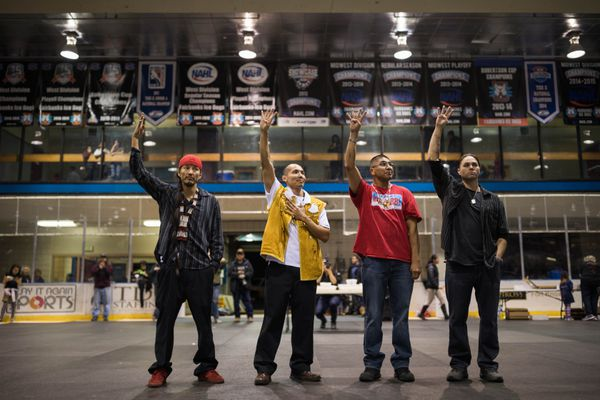 The Fairbanks Four, from left, George Frese, Marvin Roberts, Eugene Vent and Kevin Pease, raise four fingers as a symbol of their struggle during a potlatch held in their honor at the Big Dipper arena in Fairbanks on Wednesday, Oct. 19, 2016. The men spent 18 years in prison for a 1997 murder they say they didn't commit, and were released after a December 2015 settlement with the state of Alaska. (Loren Holmes / ADN)