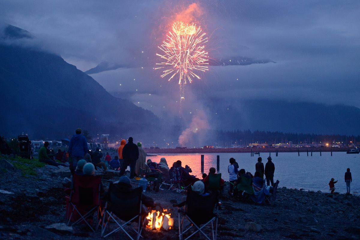 Fireworks burst over the boat harbor in Seward at midnight on July 4, 2015. Hundreds of campers and visitors gathered to watch on the shoreline. (Marc Lester / ADN)