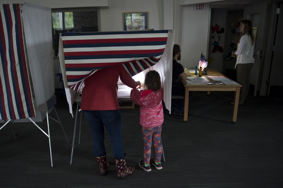 Kelly Quisenberry votes while her daughter, Emma, 4, holds a headlamp at the Rabbit Creek Elementary polling place during a power outage in the vicinity on August 21, 2018. (Marc Lester / ADN)
