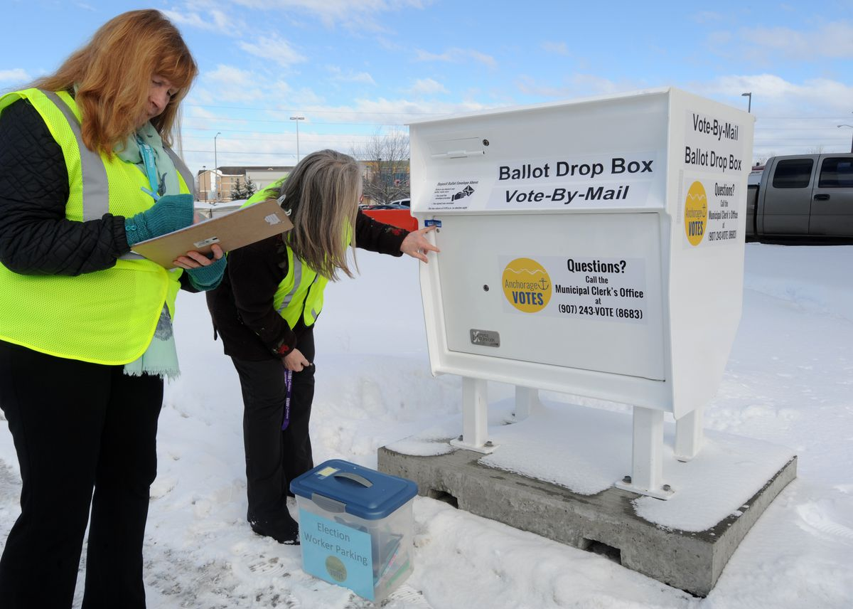 Anchorage election officials Marcia Harth, left, and Cindy Hawkins prepare to unlock the ballot drop box outside Loussac Library on Tuesday, March 13, 2018. (Anne Raup / ADN)