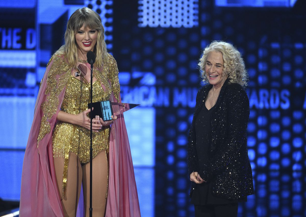 Taylor Swift, left, accepts the award for artist of the decade at the American Music Awards on Sunday, Nov. 24, 2019, at the Microsoft Theater in Los Angeles. Looking on at right is Carole King. (Photo by Chris Pizzello/Invision/AP)