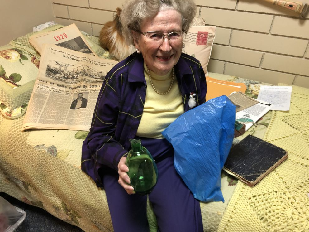 Lucy Whitehead holds a vase she saved that was broken in the 1964 Good Friday Earthquake, with newspapers from the quake, in her room at the Anchorage Pioneer Home, December 12, 2018. (Charles Wohlforth / ADN)