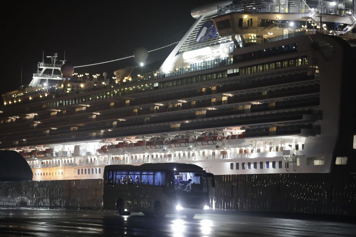 A bus carrying passengers from the quarantined Diamond Princess cruise ship leaves a port in Yokohama, near Tokyo, Monday, Feb. 17, 2020. (AP Photo/Jae C. Hong)