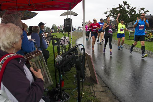 Anchorage RunFest participants cheer for The Alaska Button Box Gang music group performing at Westchester Lagoon on Sunday, August 21, 2016. The event included a variety of entertainers located throughout the course. (Sarah Bell / Alaska Dispatch News)