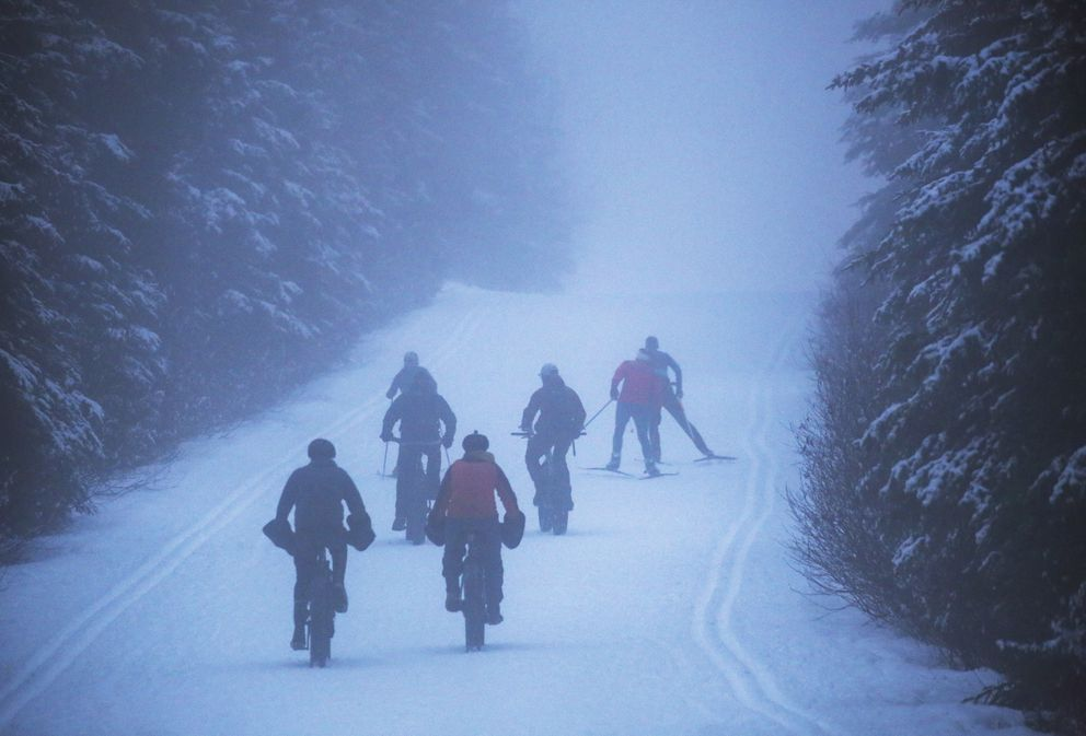 Fat-tire bikers approach skiers on the Gasline Trail near Hilltop Ski Area as a layer of fog clings to the trail in Anchorage on Thursday, Nov. 12, 2020. (Emily Mesner / ADN)