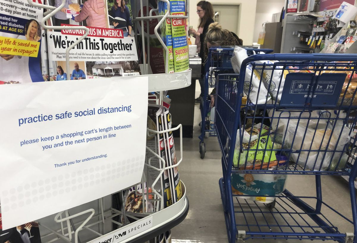 A sign alerts shoppers to practice social distancing, due to the coronavirus, while in the checkout line at a grocery store, Saturday, March 28, 2020 in Troy, Mich. (AP Photo/Carlos Osorio)