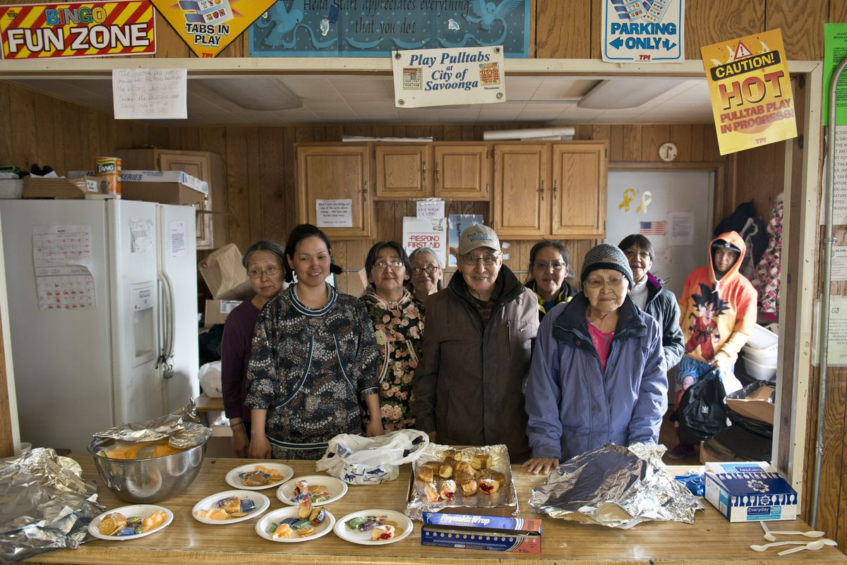 Chester Noongwook, center, a member of the crew that landed Savoonga's first whale 45 years ago, stands with family and friends during the celebration. Savoonga residents gathered onFriday at the city building for a celebration to honor the 45th anniversary of the landing of the village's first whale. (Marc Lester / Alaska Dispatch News)