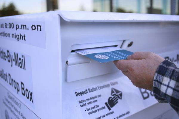 A man places his completed 2020 general election ballot into the dropbox outside the State Division of Elections office, located at 2525 Gambell St., in Anchorage on Oct. 13, 2020. (Emily Mesner / ADN)