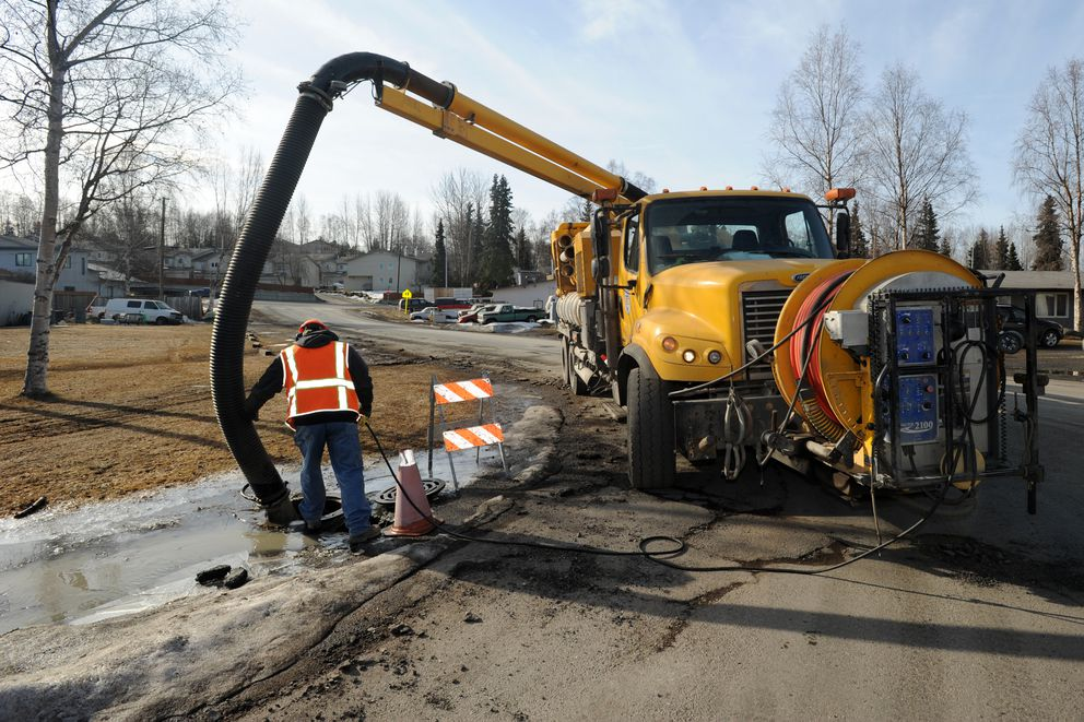 Ron Butler of the city's Street Maintenance Division positions a hose while operating a vacuum truck to remove water from a disabled storm drain at Nathan Drive and East 75th Avenue on April 21 in South Anchorage. (Erik Hill / Alaska Dispatch News)