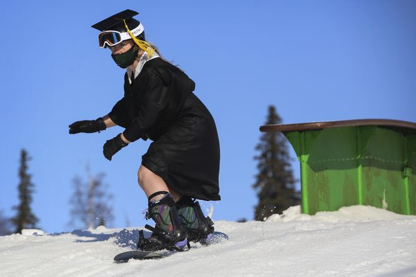 Shelbee Davis clears a ramp while snowboarding at Hilltop Ski Area in Anchorage on Friday, April 16, 2021. Davis hit the slopes after attending her Wayland Baptist University graduation Friday after it was postponed last year due to the pandemic. (Emily Mesner / ADN)