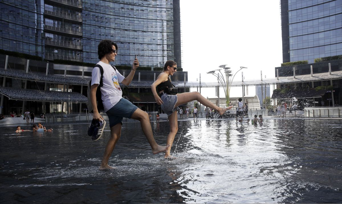 People cool off in a fountain in Milan, Italy, during a record-breaking heat wave on July 24, 2019. (AP Photo/Luca Bruno)