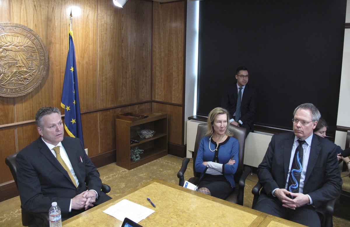 Alaska Gov. Mike Dunleavy, left, speaks to reporters during a news conference on Tuesday, April 9, 2019, in Juneau, Alaska. Also seated at the table are Donna Arduin, Dunleavy's budget office director, and Bruce Tangeman, his Revenue commissioner. Dunleavy spokesman Matt Shuckerow is standing in the background. (AP Photo/Becky Bohrer)