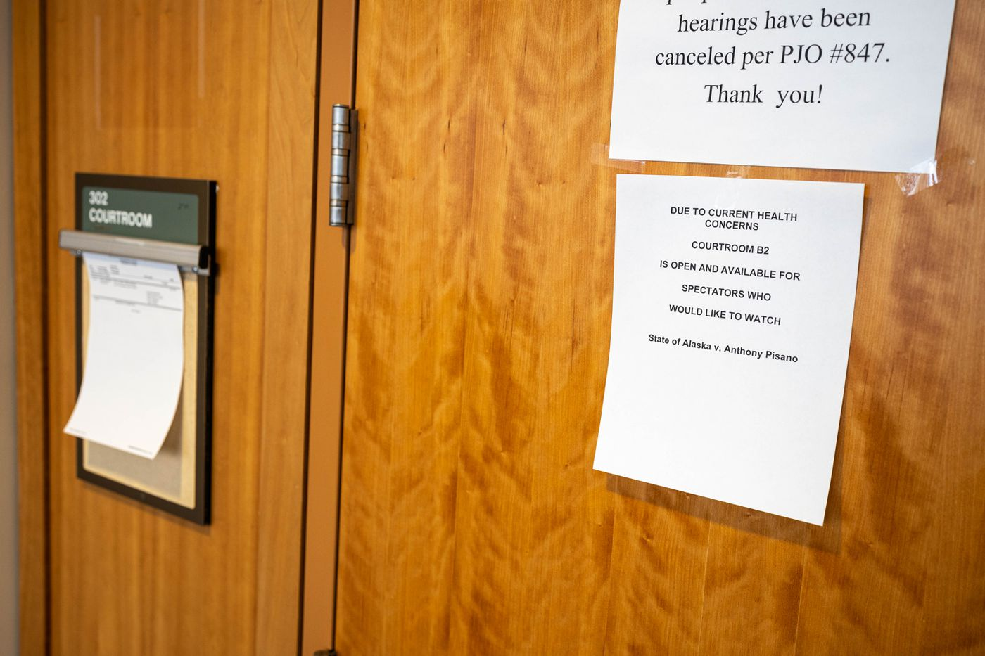A sign on the door of a courtroom instructs people that due to current health concerns, the room is closed to the public and that they should watch the proceedings over a live video feed on Wednesday, March 18, 2020 at the Nesbett Courthouse in Anchorage. The case being tried is State of Alaska v. Anthony Pisano, who is charged with murder. (Loren Holmes / ADN)