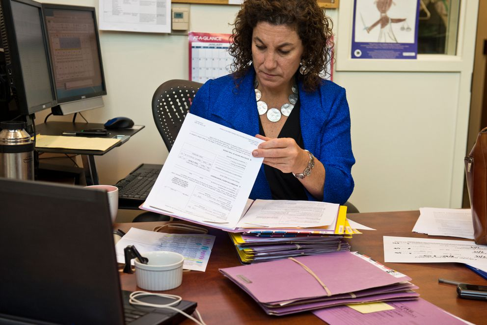 Anchorage Magistrate Judge Suzanne Cole reviews case files before the start of domestic violence court on a day in June. (Marc Lester / Alaska Dispatch News)