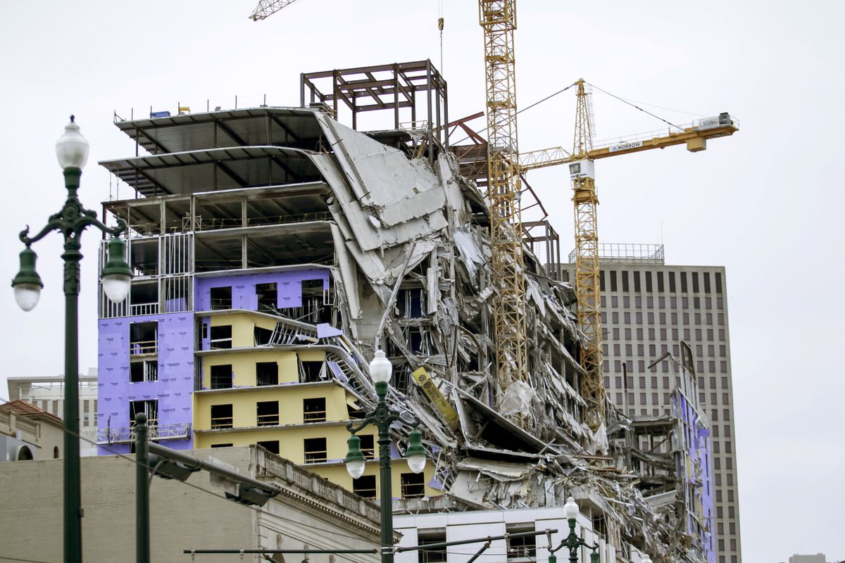 Debris hangs on the side of the building after a large portion of a hotel under construction suddenly collapsed in New Orleans on Saturday, Oct. 12, 2019. (Scott Threlkeld/The Advocate via AP)