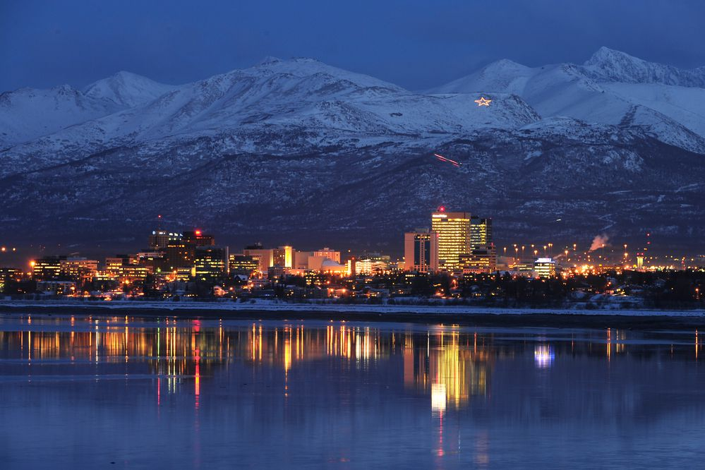 The JBER star shines on the slopes of the Chugach Mountains as they rise above the Anchorage skyline which is reflected in the waters of Cook Inlet just after sunset on Monday, January 6, 2014. (Bob Hallinen / ADN)