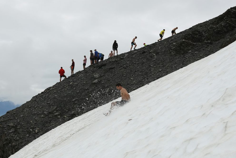 A racer slides down the snow as others work their way up the ridgeline in Monday's men's race. (Loren Holmes / Alaska Dispatch News)