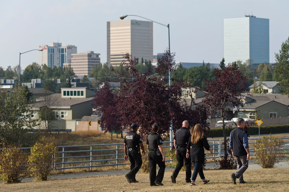 Anchorage Police officers and city officials walk near camps along A Street. (Marc Lester / ADN)