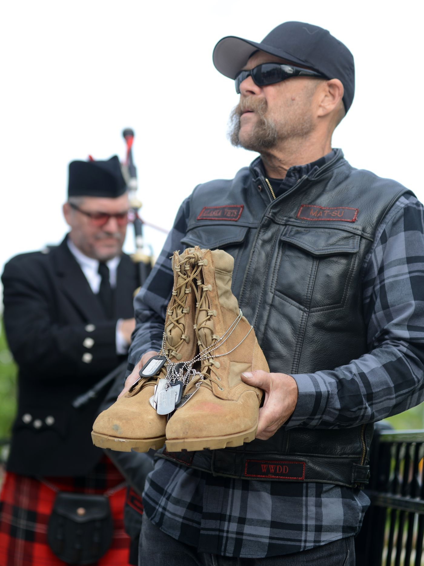 Navy veteran Sidestep, a member of the Alaska Vets Motorcycle Club, prepares to bring the boots forward for the Fallen Warrior ceremony during the Memorial Day remembrance on the Park Strip. Pipe Major Ian White, of the Crow Creek Pipes waits to play Amazing Grace for the fallen warrior. (Anne Raup / ADN)