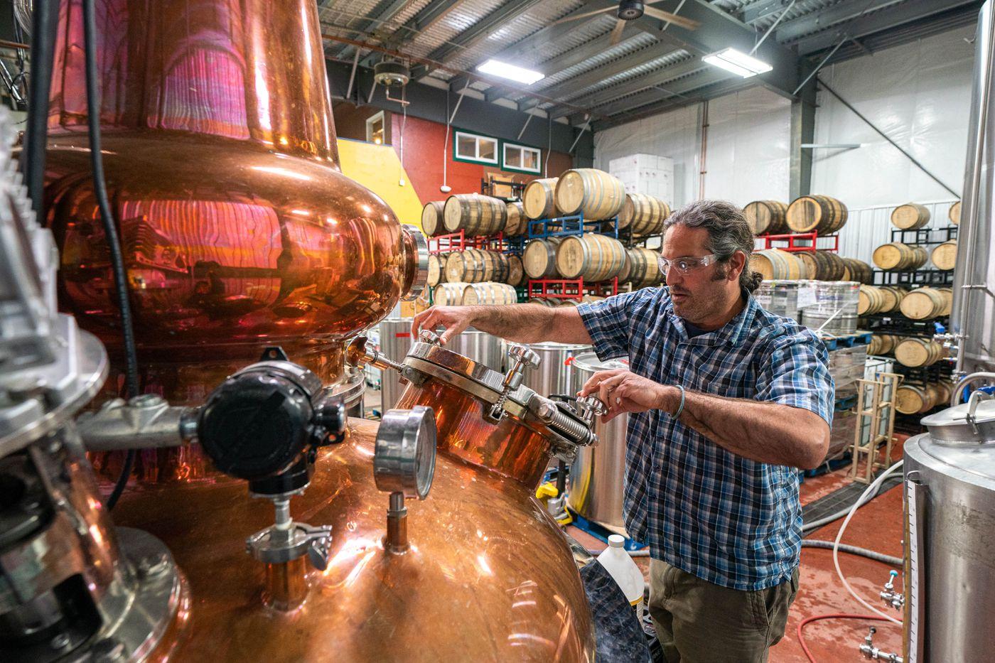 Denali Brewing owner Sassan Mossanen puts de-foamer in a still on Thursday, May 21, 2020 in Talkeetna. The brewery also operates a distillery and brewpub. (Loren Holmes / ADN)