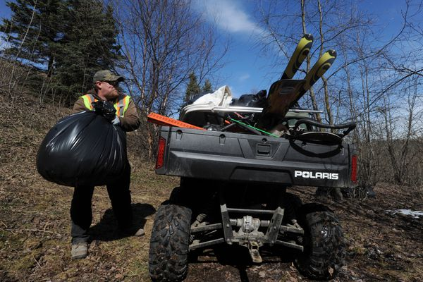 Parks & Recreation worker Will Miller tosses a garbage bag in the back of a Ranger filled with items, including a pair of skis, that were remove from an abandoned homeless camp on Thursday, April 25, 2019. (Bill Roth / ADN)