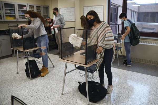 FILE - In this March 18, 2021, file photo, students in teacher Christopher Duggan's science class clean their work areas at the end of class at Windsor Locks High School in Windsor Locks, Conn. The Centers for Disease Control and Prevention relaxed its social distancing guidelines for schools Friday, March 19, saying students can now sit 3 feet apart in classrooms. The new guidelines also remove recommendations for plastic shields or other barriers between desks. (AP Photo/Jessica Hill, File)