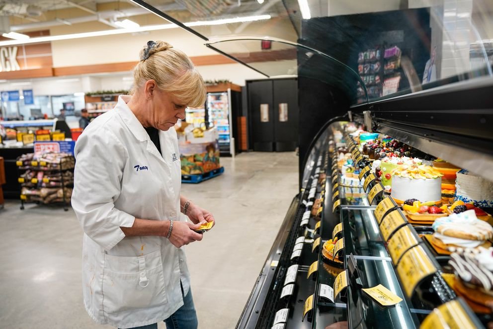 Tracy Moore puts price tags on the bakery case in the Midtown Mall Carrs store. (Loren Holmes / ADN)
