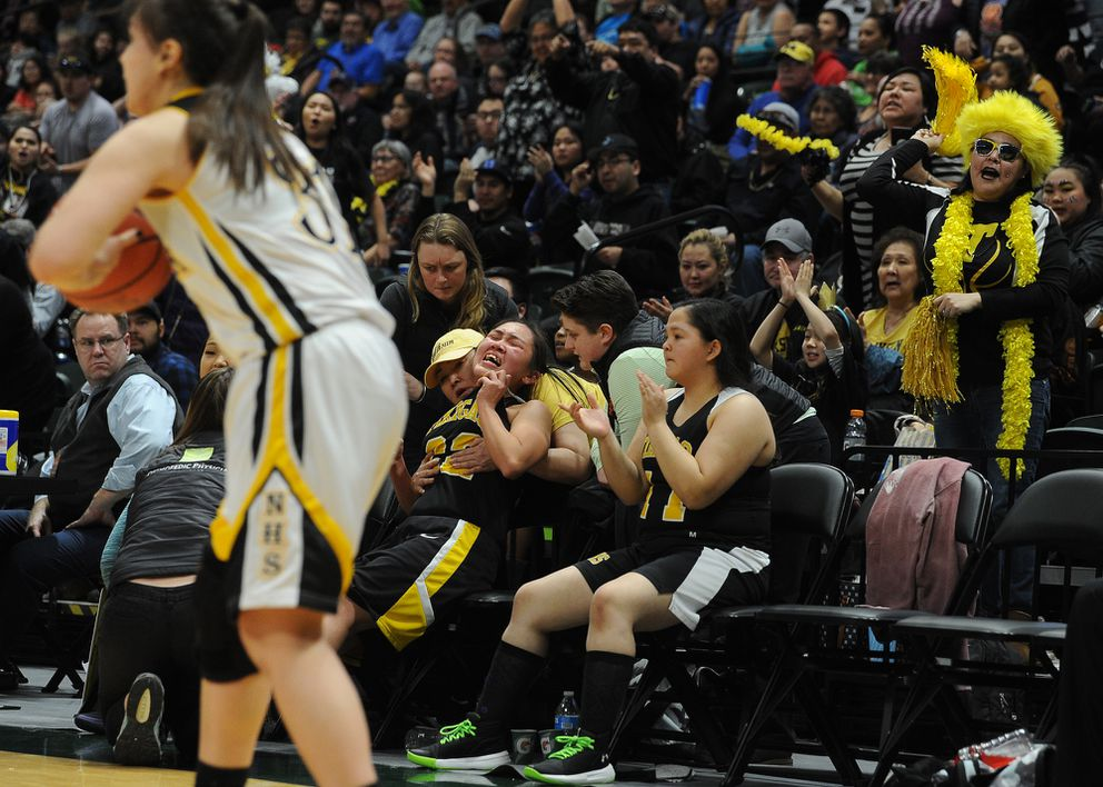 Tikigaq's Bridgette Oviok leans back in pain after going to the bench with calf cramps. (Photo by Bob Hallinen)