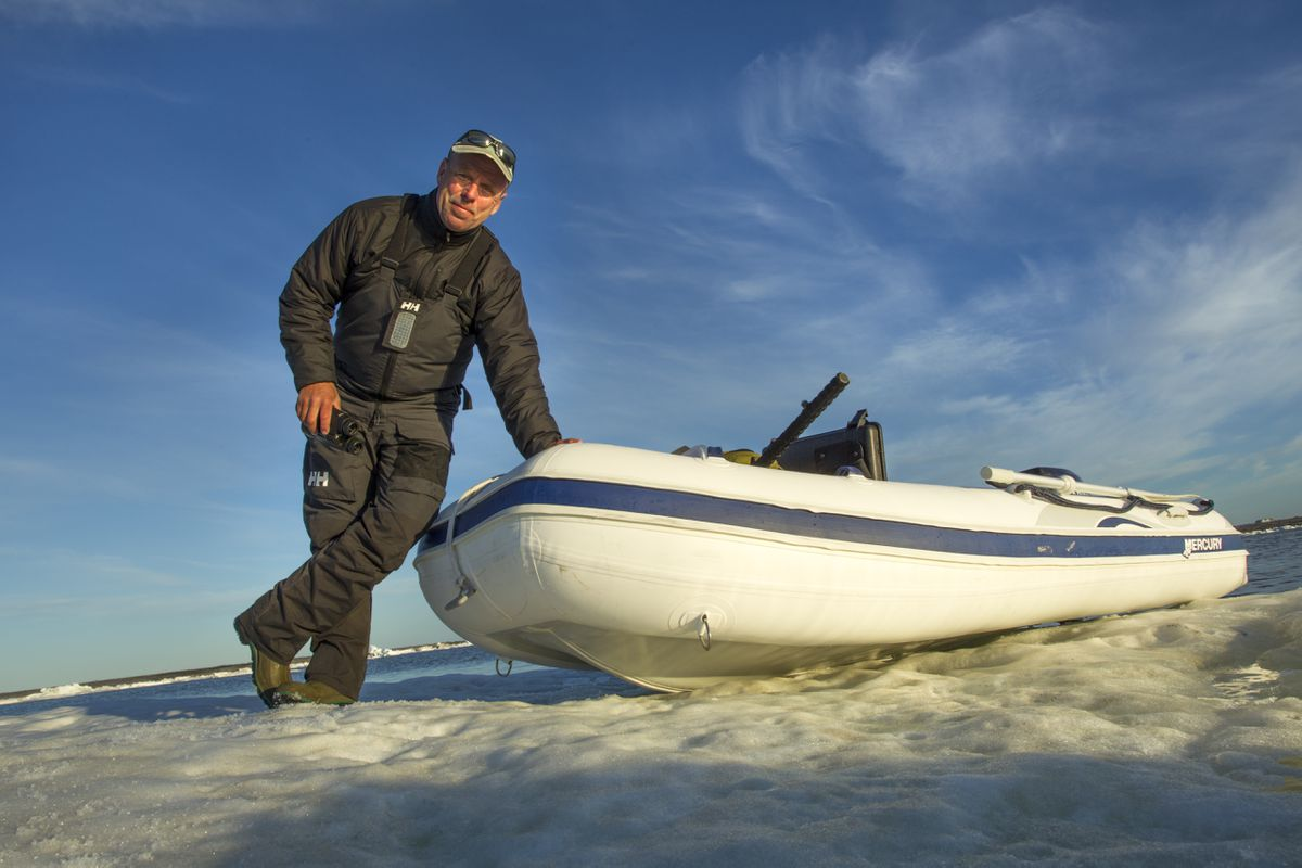 Self-portrait of photographer Paul Souders with an inflatable expedition boat on melting sea ice on Hudson Bay. (Paul Souders / WorldFoto)