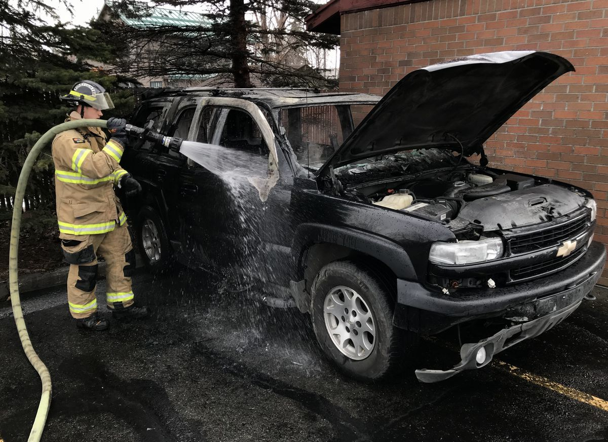 "Anchorage firefighter Brett Keene tends to a vehicle fire Wednesday morning, April 18, 2018, in the parking lot of the Church of Jesus Christ of Latter-day Saints off Baxter Road in East Anchorage. The stolen vehicle is ""similar to the getaway vehicle"" used in two Anchorage gas station robberies on Tuesday, police said. (Bill Roth / ADN)"