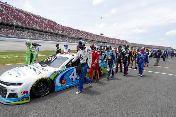 Nascar drivers Kyle Busch, left, and Corey LaJoie, right, join other drivers and crews as they push the car of Bubba Wallace to the front of the field prior to the start of the NASCAR Cup Series auto race at the Talladega Superspeedway in Talladega Ala., Monday June 22, 2020. In an extraordinary act of solidarity with NASCAR's only Black driver, dozens of drivers pushed the car belonging to Bubba Wallace to the front of the field before Monday's race as FBI agents nearby tried to find out who left a noose in his garage stall over the weekend.(AP Photo/John Bazemore)