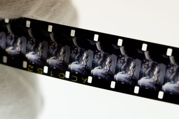 A piece of film strip is examined in the Film Lab at the Museum of the North in October 2015. (Leonard Kamerling)