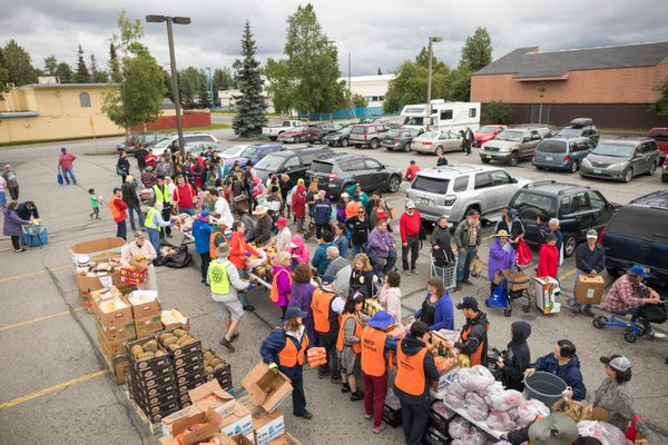 Over 100 households wait in line to receive food from the Food Bank of Alaska's Mobile Food Pantry Saturday, Aug. 12, 2017 at the Fairview Rec Center. Volunteers from Anchorage East Rotary were on hand to organize the food distribution. (Loren Holmes / Alaska Dispatch News)