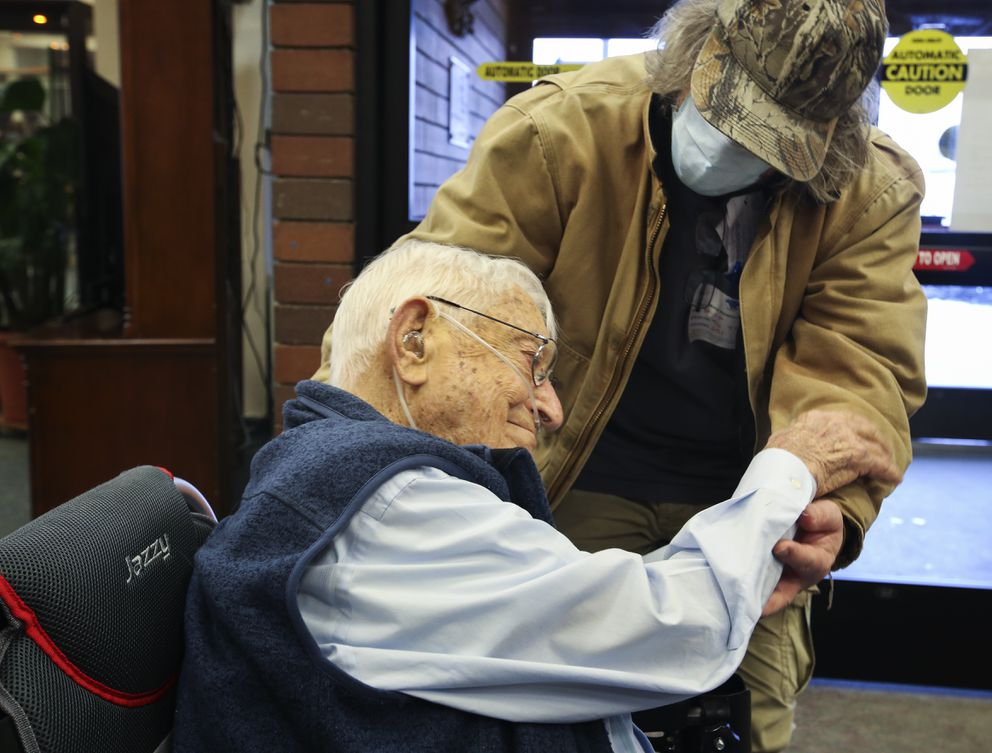Philip Badger hugs his father, Billy Badger, after visiting him at the Anchorage Pioneer Home on Wednesday, Feb. 3, 2021. 'Way overdue, but it's the world we live in, ' said Philip, who hasn't been able to visit his father for months due to the pandemic. (Emily Mesner / ADN)