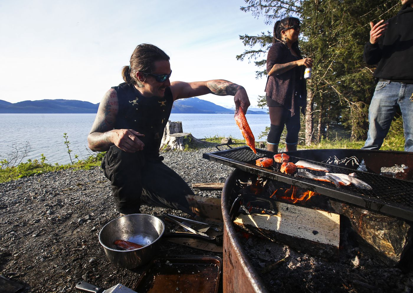 Matt Honkola places a piece of king salmon he harvested during the first Copper River opener on a grill while cooking for friends at Hartney Bay in Cordova on Tuesday, May 18, 2021. (Emily Mesner / ADN)