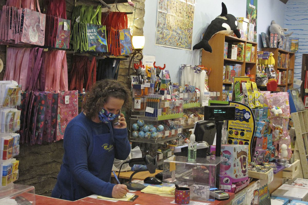 Alicia Smith, owner of Juneau's Imagination Station, jots notes while taking a call on Friday, April 24, 2020, in Juneau, Alaska. She said the specialty toy store has been doing curbside pickup and starting Tuesday will offer limited store hours with limited numbers of shoppers inside. (AP Photo/Becky Bohrer)