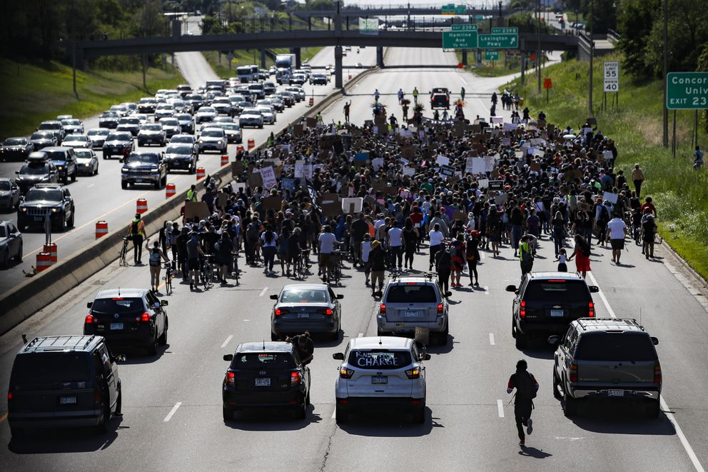 Protesters march down Highway 94, Sunday, May 31, 2020, in St. Paul, Minn. Protests were held in U.S. cities over the death of George Floyd, a black man who died after being restrained by Minneapolis police officers on May 25. (AP Photo/John Minchillo)